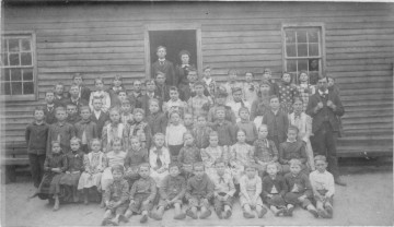Flat Rock School.<br> Identifications as given by Annis Jones Humphries: Seated center, on ground in large black hat, Annis Jones Humphries,  To her left, Aunt Bernice and Ruth Huie.<br> Front row standing, 3rd from left, Aunt Laura; seated, bearded man with cane is Grandfather Samuel Lawson McNair with wife, Martha Jane Nisbet.<br> Auntie (Emma Jones) is standing behind man holding baby.<br> Top row left to right, Uncle Chester Jones; 5th from left, John D. Humphries; Lillie Marvin Jones;<br> Grandfather John Franklin Jones; head by his hand is Grandmother Eliza Oregon McNair; then Aunt Nonnie Lassiter; Aunt Nettie Huie; Uncle Walter McNair.