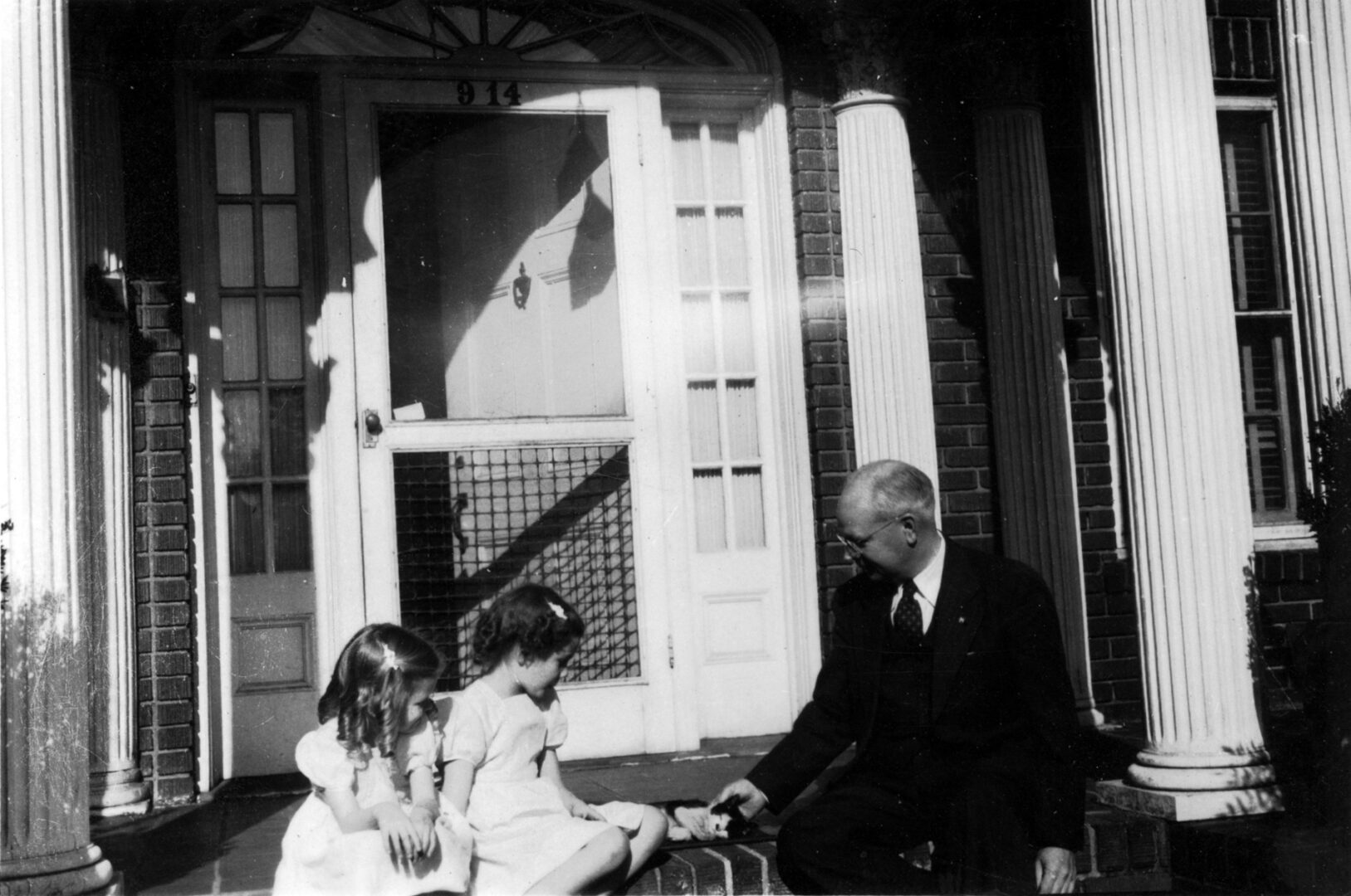 Demaris, Lillie, and Daddy with kitten on Atlanta porch